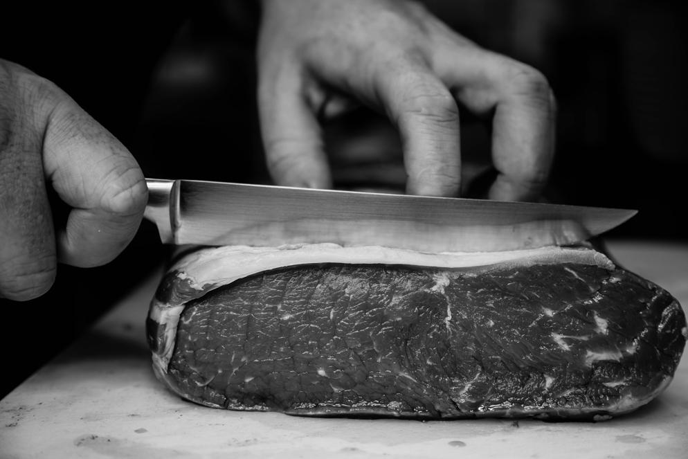 Metzger Meino. Der Küchenchef bei der Fleischzubereitung